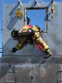 Hanging from a ladderless window until a ladder can be brought to the firefighter in distress.